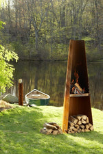 Wittus outdoor Phoenix Grill on lawn in front of river with green boat