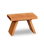 Solid cherry wood step stool with angled legs.