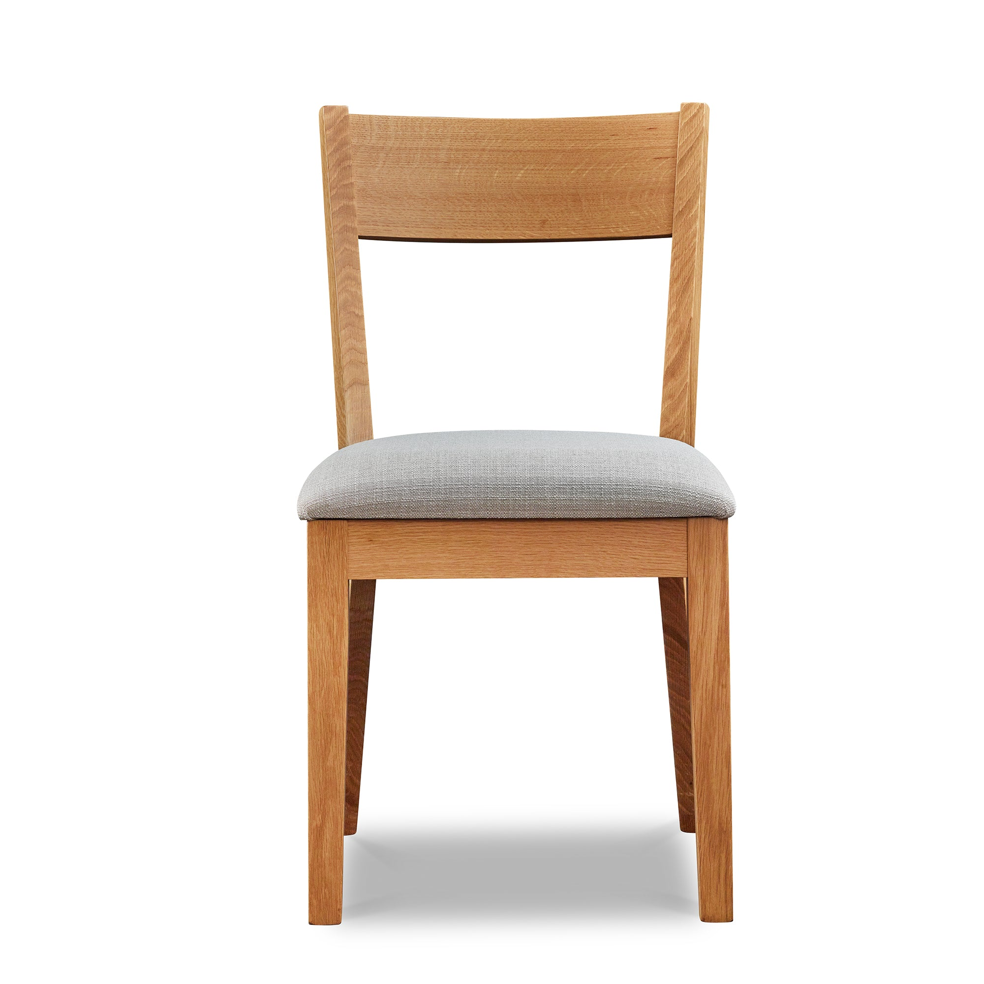 Front-facing view of a modern Scandinavian style solid wood dining chair, in white oak with grey cushion, from Maine's Chilton Furniture Co.