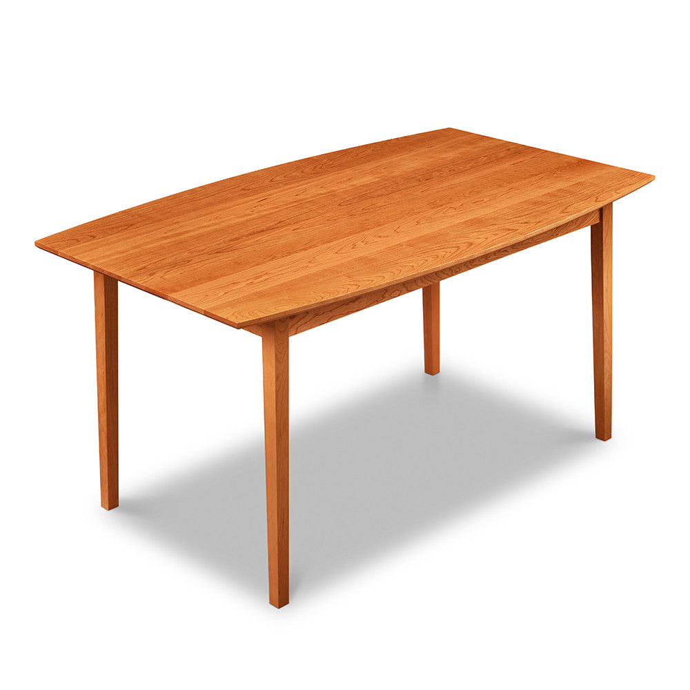 Cherry wood dining table with curved boat-shaped edges and clean tapered legs, from Maine's Chilton Furniture