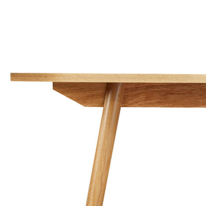 Detail of Mid-century modern Fjord dining table angled legs and apron in solid white oak from Chilton Furniture Co.