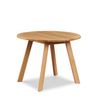 Round modern dining table with angled legs in white oak, from Maine's Chilton Furniture Co.