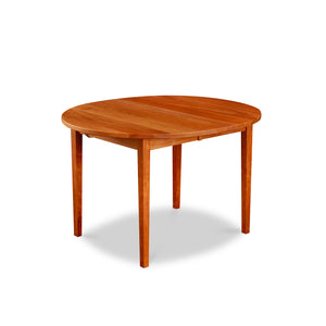 Cherry wood extension table with simple Shaker legs and round top from Maine's Chilton Furniture Co.