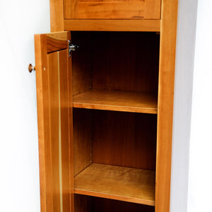 Open door of cherry chimney cupboard showing storage space and two shelves inside