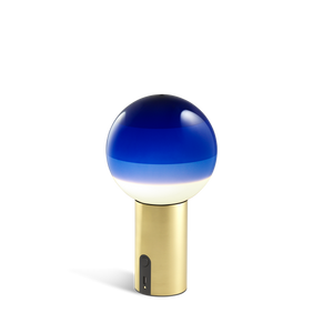 Small portable lamp with brass base and blue glass sphere with layered shades from white to dark blue