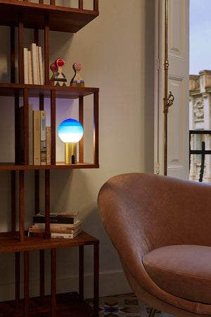 Blue portable glass sphere lamp on geometric wooden bookcase