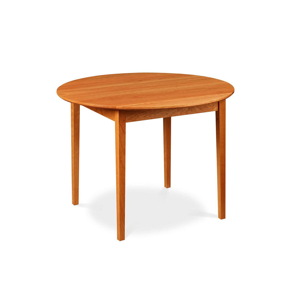 Small Shaker style dining table with tapered legs and round top, made of cherry wood