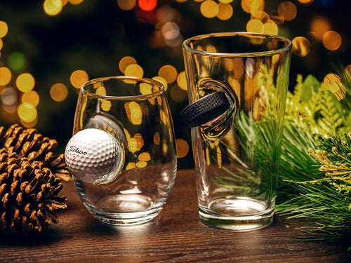 BenShot Golf Ball Wine Glass and BenShot SlapShot Hockey Puck Pint Glass on a table next to Christmas decorations with Christmas lights in the background.
