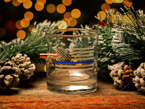 BenShot Thin Blue Line Rocks Glass on a table next to Christmas decorations with Christmas lights in the background.