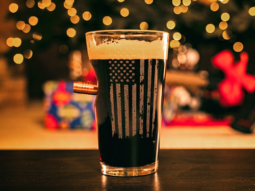 BenShot Patriotic Pint Glass on a table in front of a Christmas tree.