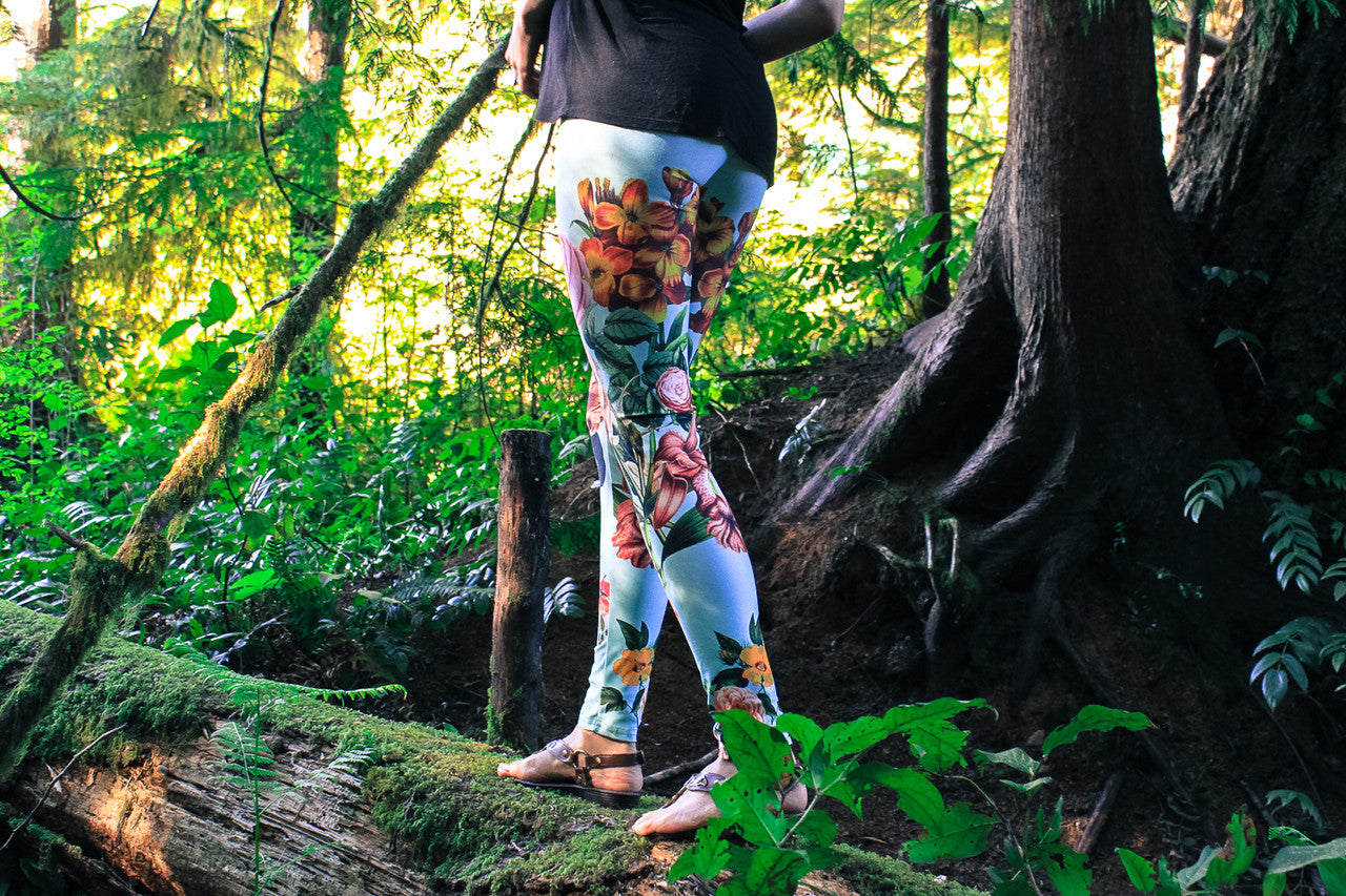 flora aura leggings by wildandroaming - woman wearing leggings in the forest walking on a log as the sun sets