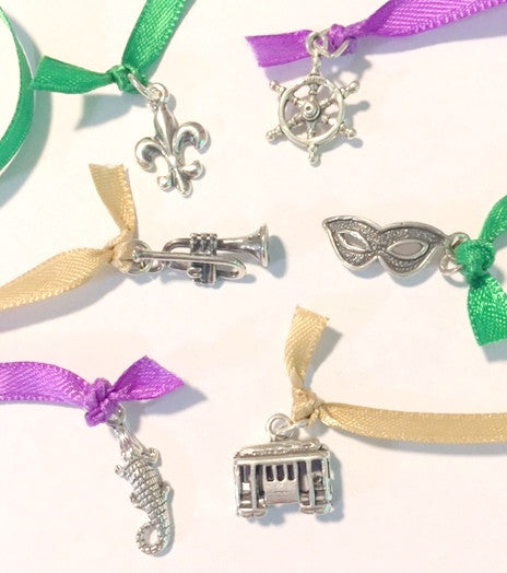 sterling New Orleans themed wedding cake pull charms with purple gold and green ribbons