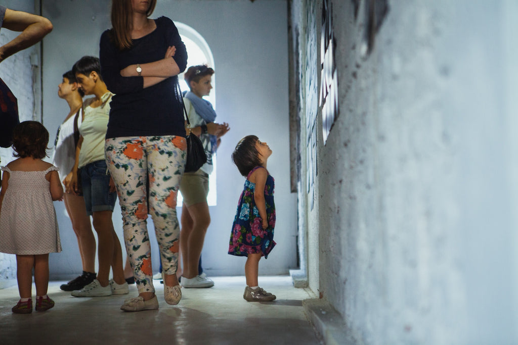 little girl looks at painting photography by viktor ivanov