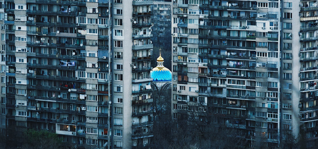mosque between blue buildings photography by viktor ivanov