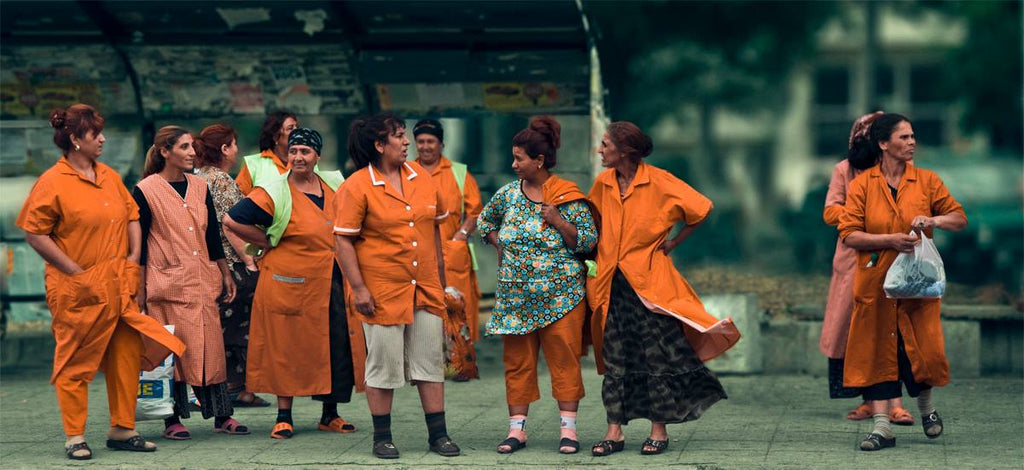 Women in orange uniform waiting for a bus photography by viktor ivanov