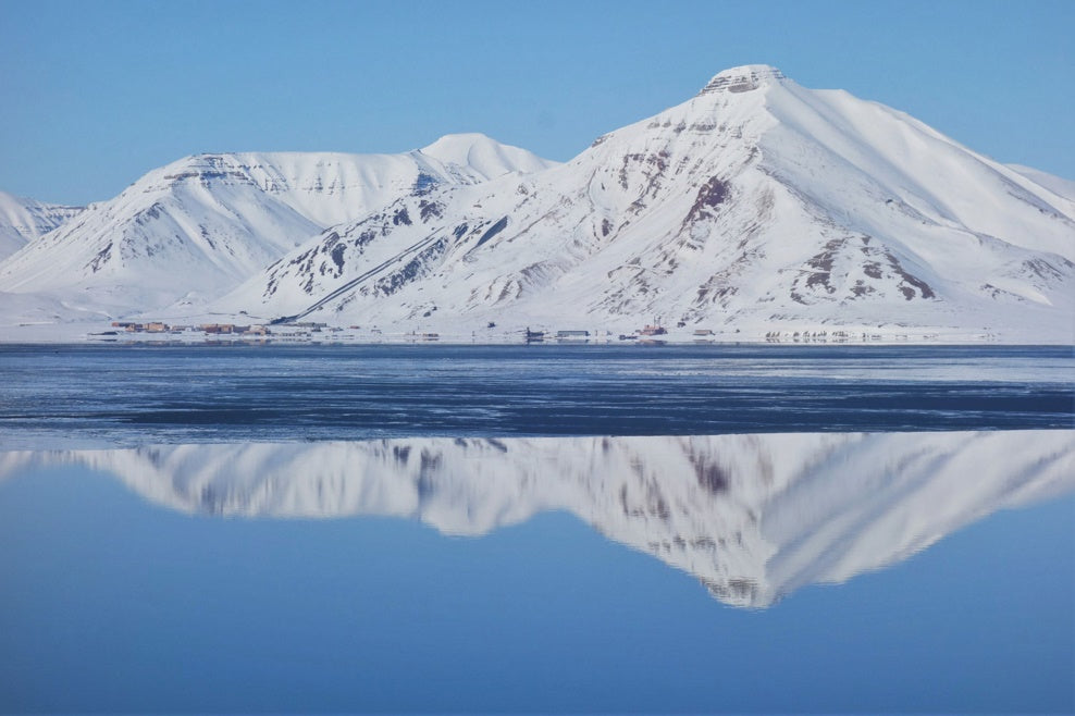 Icy mountain reflecting off water photography by Adam Saligman