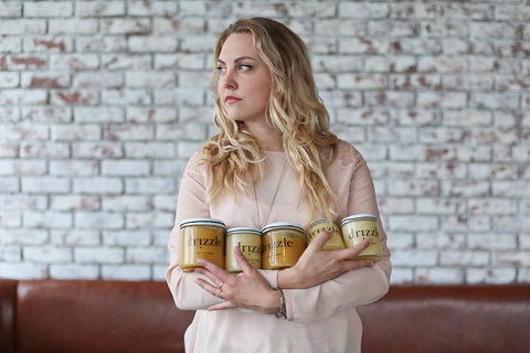 Drizzle Honey Owner and Founder Aja Horsley holding three jars of Raw Honey