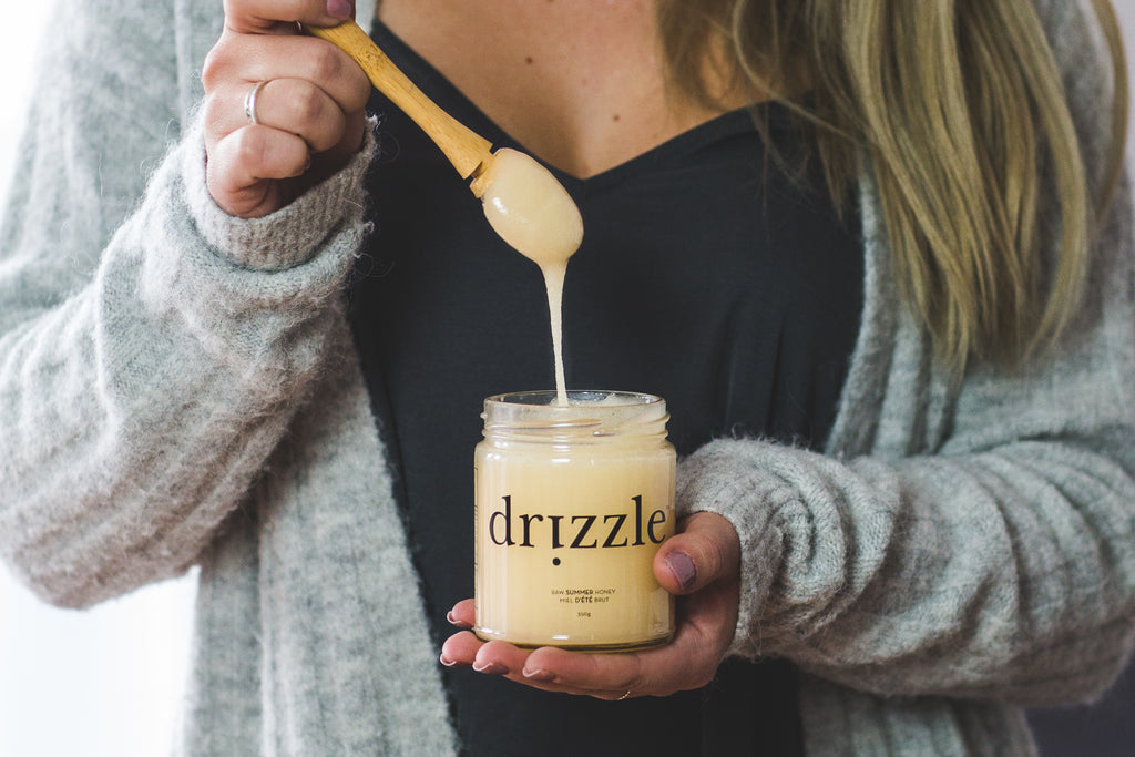 Drizzle Bamboo Honey Dipper drizzling from a jar of Summer Honey