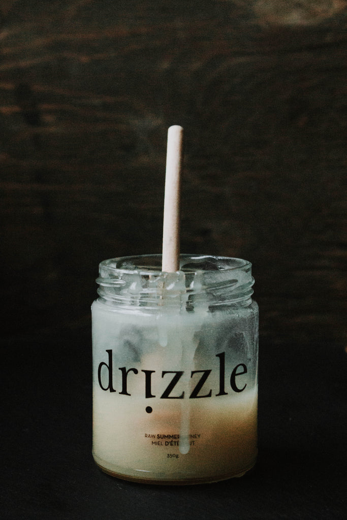Drizzle Summer honey in a glass jar with a honey dipper