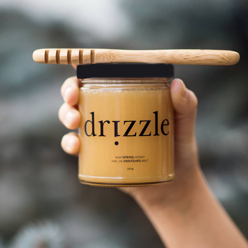 Drizzle Golden Raw Honey being held with a honey dripper on top.