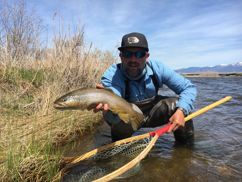 Brian Rosenberg posing with a brown trout caught on the Madison River during a guided float fishing trip near Ennis Montana