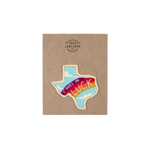 "cross stitched patch in the shape of the state of texas with a rainbow stretched across that featured the word ""Luck"""