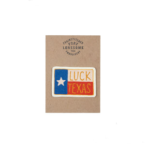 cross stitched luck texas patch on top of a summarized texas flag