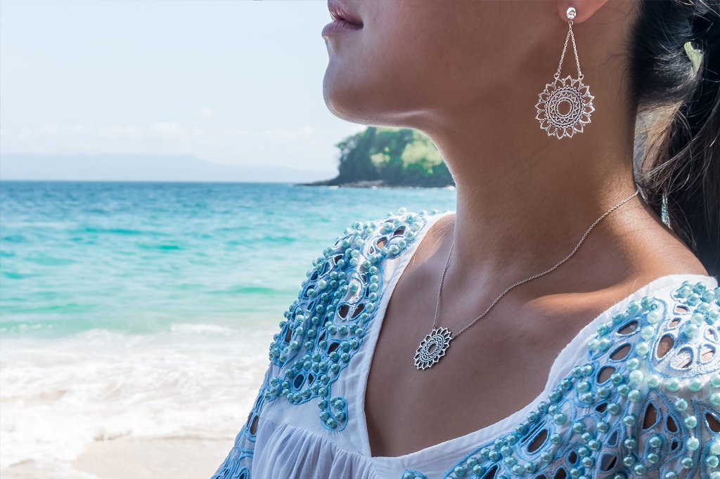 lifestyle photo sterling silver sun mandala earrings and necklace bohemian style boho chic beach blue ocean