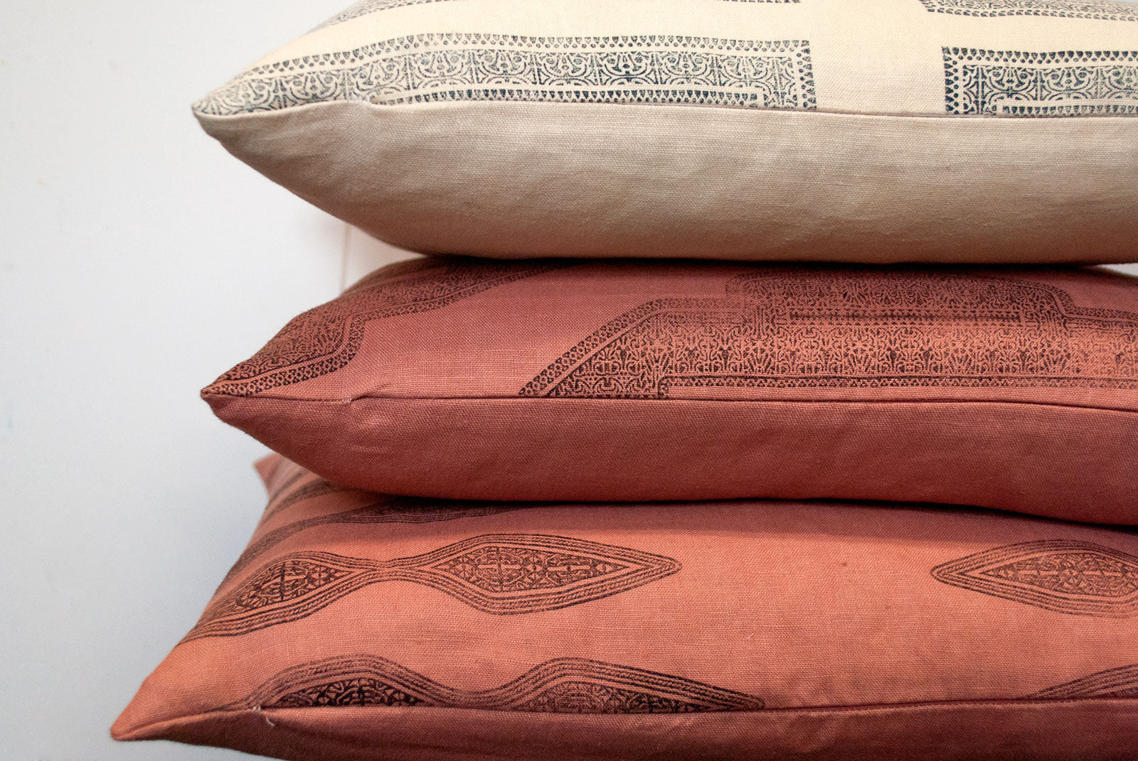 a stack of pillows in the studio of textile designer, susan connor