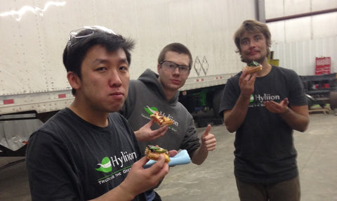The Hyliion team eating pizza on the factory floor.