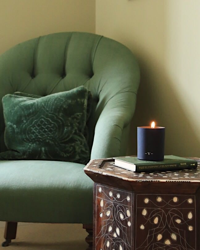 A scented candle with a dark blue jar next to a green chair.