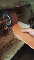 leather sandal sole edges being smoothed in workshop