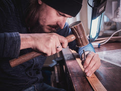 Man imprinting a handcrafted leather belt