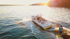 Family on a boat in the ocean while the sun sets