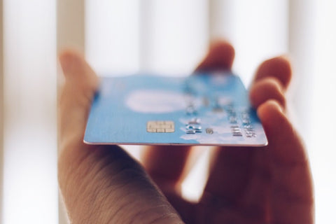 Side view of hand holding credit card