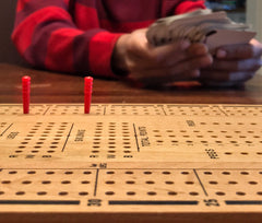 Close up plain wood cribbage board with two red pegs