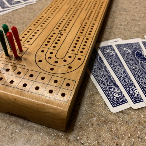 Close up of cribbage board with pegs in it next to cards