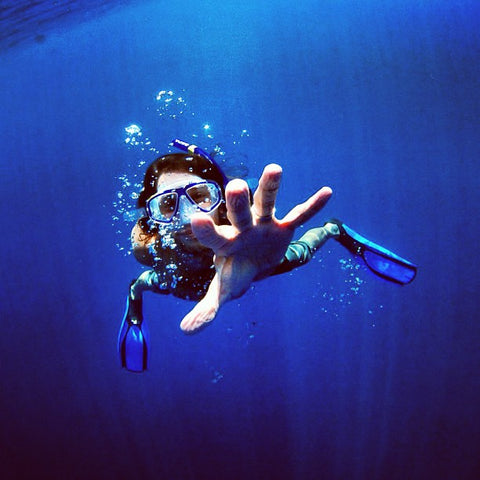 Girl in diving gear ruching out to camera