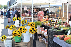 Tables of flowers, vegetables, and fruit under tents at a farmers market