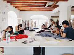 Students making clothes around a table during a fashion class
