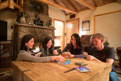 Family happily playing cards while sitting around the table