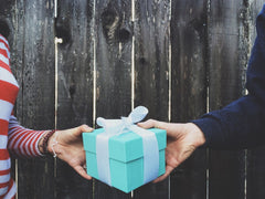 A woman and man exchanging a teal giftgiftboxbox