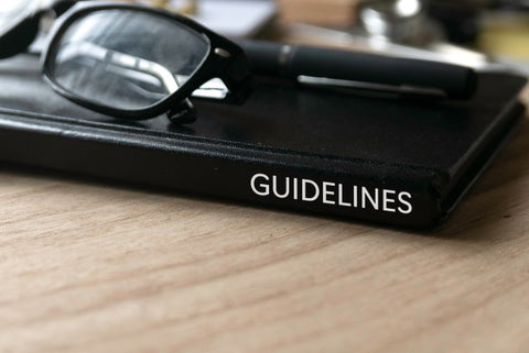 """Side of black """"Guidelines"""" book with glasses on top of it"""