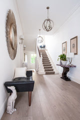 Hallway in a home with a mirror and home decor hanging