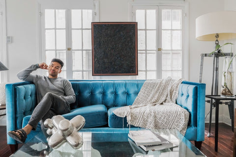 Man lounging on side of blue couch with coffee table in front of him