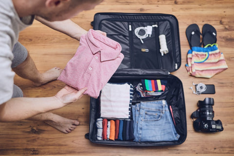 Man packing clothes in suit case