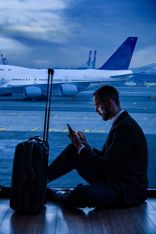 Man sitting on ground next to suitcase at night in airport in front of window