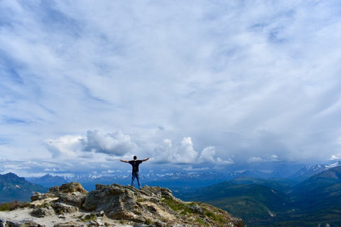 Man standing on top of mountain with open arms facing blue sky