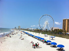 Beach umbrellas lined up on a beach with a Ferris wheel in the background at Myrtle Beach