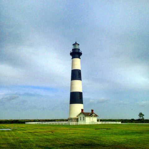 Outer Banks Blue and White striped light house next to small house in field